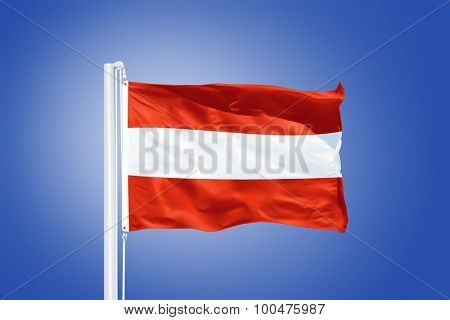 Flag of Austria flying against a blue sky.