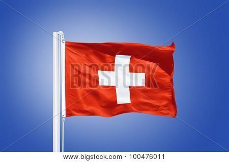 Flag of Switzerland flying against a blue sky.