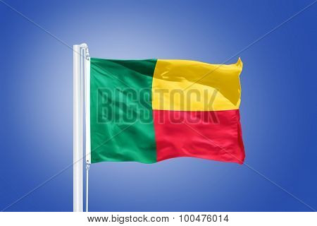 Flag of Benin flying against a blue sky.