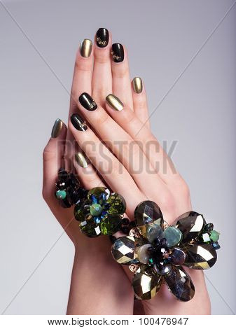 Beautiful woman's nails with  creative manicure and jewelry. Studio image
