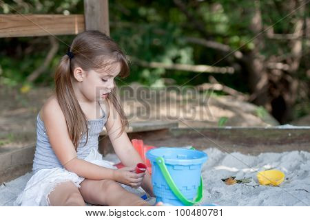 adorable little girl with two pig tails playing in sandbox in shaded backyard
