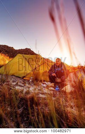 Adventure camping man cooking alone outdoors with tent, sunrise and lens flare in the mountain morning sunlight. Happy explorer enjoying a meal in the wilderness