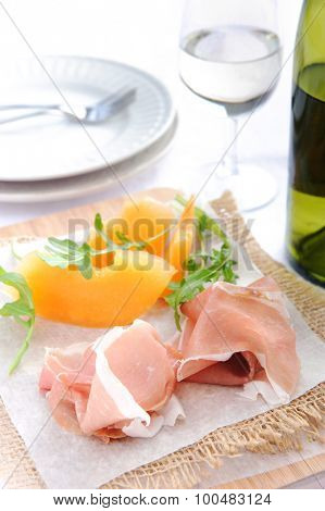 Parma ham served with cantaloupe, a common Italian antipasto with a glass of wine