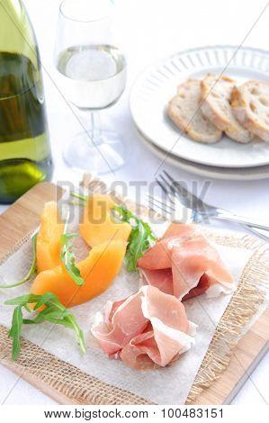 Prosciutto served with rockmelon, a common Italian antipasto with a glass of wine