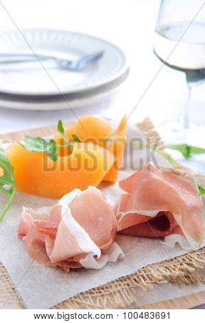Parma ham served with rockmelon, a common Italian antipasto with a glass of wine