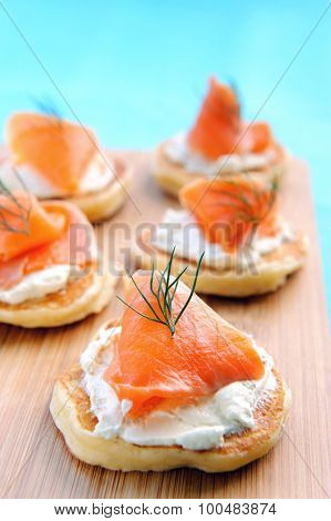 Mini pancakes blinis topped with cream cheese and smoked salmon on a wooden platter
