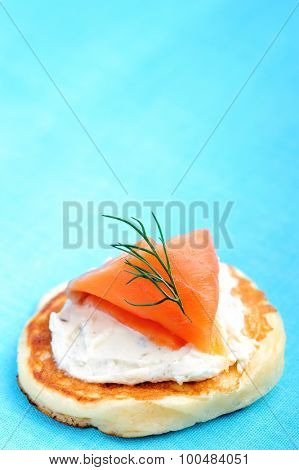 Mini pancake topped with cream cheese and smoked salmon, garnished with dill on a fresh blue background