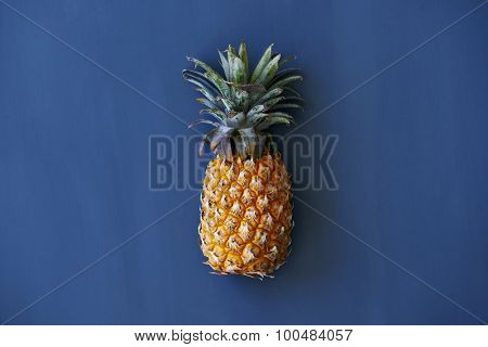 Whole pineapple against a dark blue background with copy space