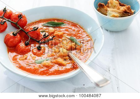Bowl of fresh delicious tomato soup with croutons and sage garnish on white rustic surface; healthy eating