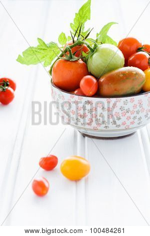 Arrangement of a variety tomatos in a bowl, cherry, roma, green, yellow, vine ripened with fresh green leaves