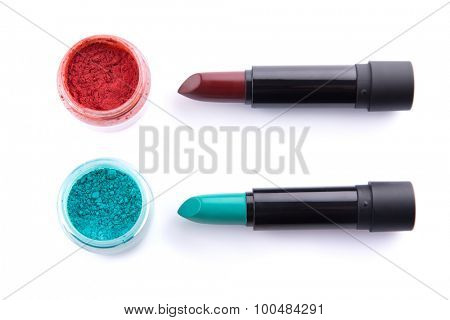 Edgy color lipsticks with matching eye shadows, top view isolated on white background