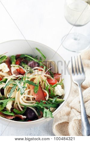 spaghetti pasta with green salad rocket, asparagus, ham and glass of white wine