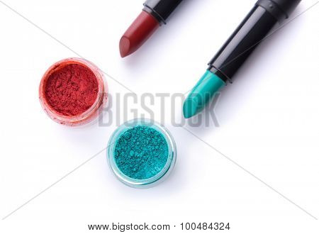 Top view of lipsticks with matching eye shadows, isolated on white background with shadow
