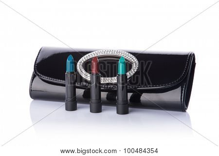 Set of fashionable lipsticks and black handbag clutch, isolated on white background