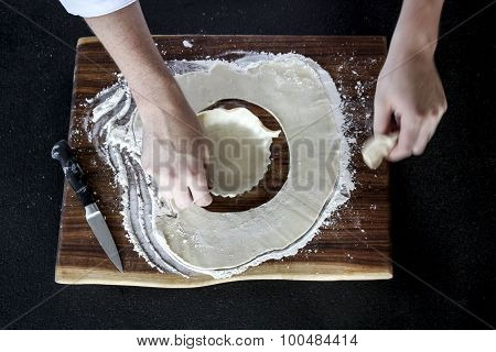 Hands cutting pastry dough