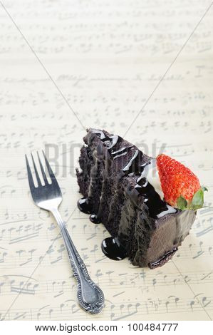 Slice of chocolate cake with chocolate fudge sauce topping and strawberry