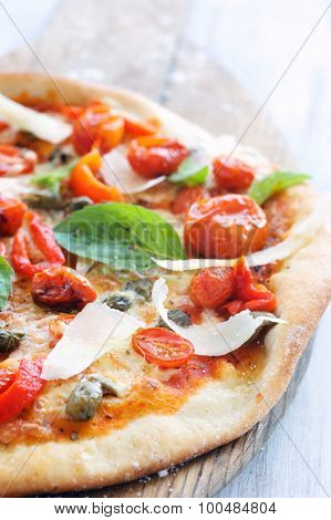 Macro close up on rustic pizza with oven roasted tomatoes, peppers, capers, basil and shaved cheese