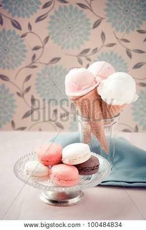 Ice cream scoops on sugar cones and french macaroons on vintage plate in soft nostalgic warm retro tone
