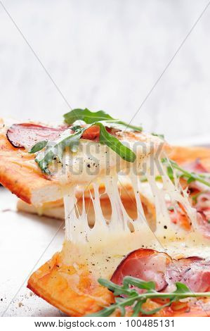 Slice of pizza lifted up with melted mozzarella, parma ham, rocket