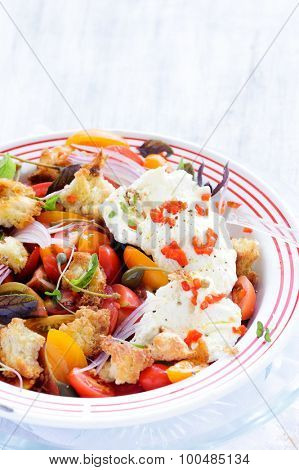 Fresh red tomatoes and mozzarella cheese salad with capers, peppers, onion, basil and croutons