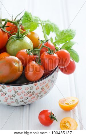 Close up tomatoes in a bowl, cherry, roma, green, yellow, vine ripened with fresh green leaves