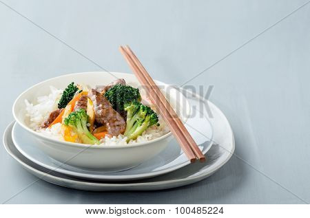 Oriental chinese beef stir fry with vegetables on white rice with pair of chopsticks, plenty of copy space