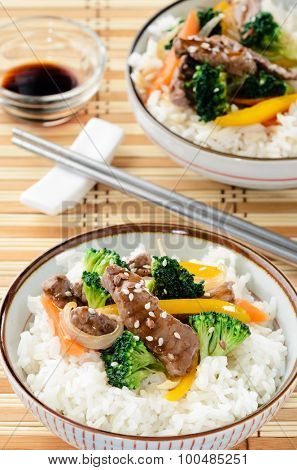 Oriental chinese beef stir fry with vegetables on white rice, bamboo mat background