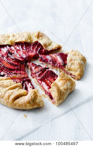 Homemade plum fruit galette, a french dessert tart pie on a rustic white background