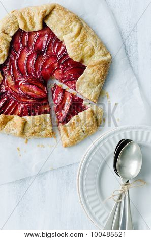 Plum galette on baking wax paper shot from overhead, whole with one serving slice cut out