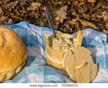wooden dish and bread on blue cloth in forest background
