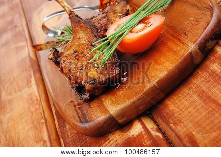 meat savory on wooden plate: roast ribs with peppers tomato and dry spices over wooden table