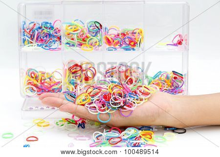 Hands And Pile Of Small Round Colorful Rubber Bands Rainbow Color For Making Rainbow Loom Bracelets