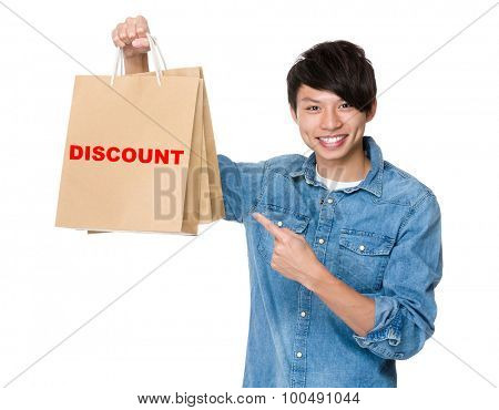 Man finger point to shopping bag for showing a word of discount