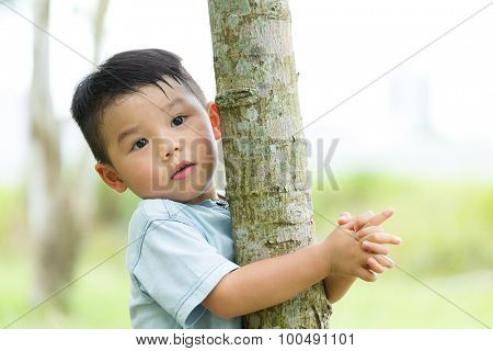 Little baby boy climb up for tree
