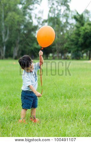 Asian little boy play balloon at outdoor