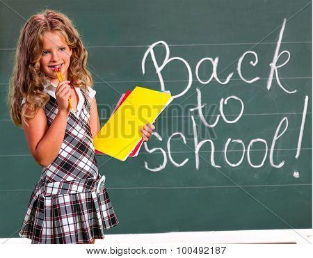 Child girl with notebook near  blackboard. Back to school.