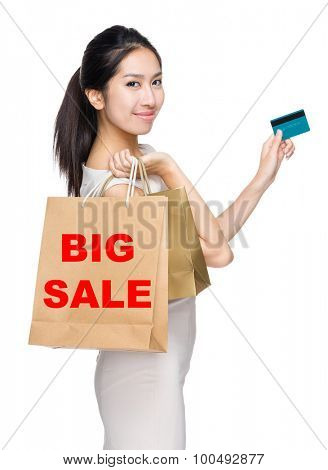 Woman with credit card and holding shopping bag for showing big sale