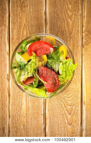 Salad with fresh vegetables, tomato and cucumbers, top view