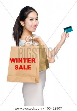 Woman with credit card and holding shopping bag for showing winter sale