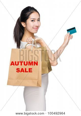 Woman with credit card and holding shopping bag for showing autumn sale