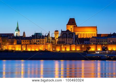 Old town of Torun at night reflected in Vistula river, Poland