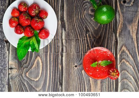 Strawberry smoothie with fresh berries on wooden background