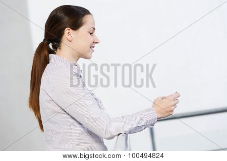 Woman standing at balcony and sending text from her mobile phone