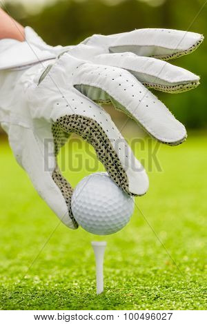 Woman's Hand Neatly Puts The Ball On Tee On Field