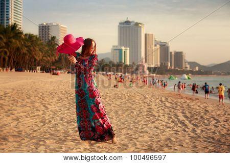 Slim Girl Demonstrates Red Hat On Beach Against City Sea