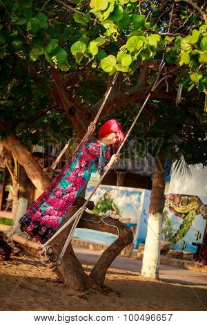Slim Girl In Long And Red Hat Swings Standing By Plant