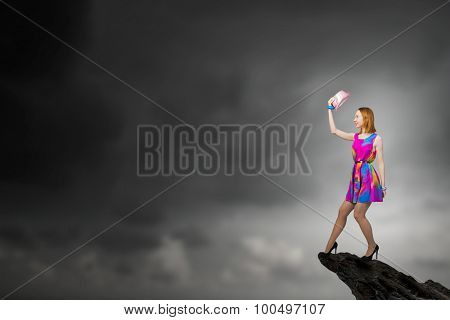 Young girl in multicolored bright dress on rock top
