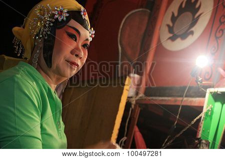 Chinese Opera Actress Is Painting Mask On His Face At Night.