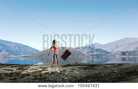 Young pretty woman walking with her vintage baggage in hand
