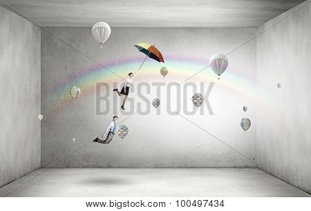 Businessman and businesswoman flying on colorful umbrella